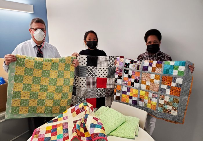 Children's Aid staff with baby quilts made for our Early Childhood program