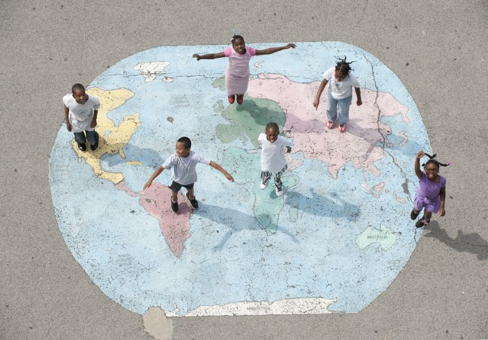 Children standing on a drawing of a world