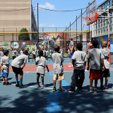 Children learning basketball on a playground